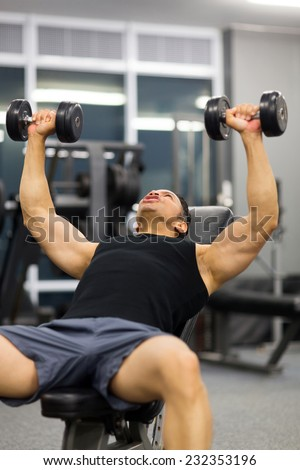 mid age man doing heavy weight exercise with dumbbells in gym