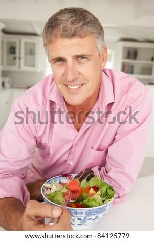 Mid age man eating salad - stock photo