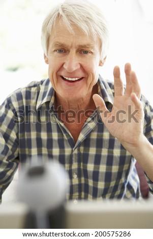Mid age man using skype - stock photo