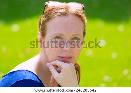 Mid age redhead woman portrait posing with green eyes on a turf grass background - stock photo