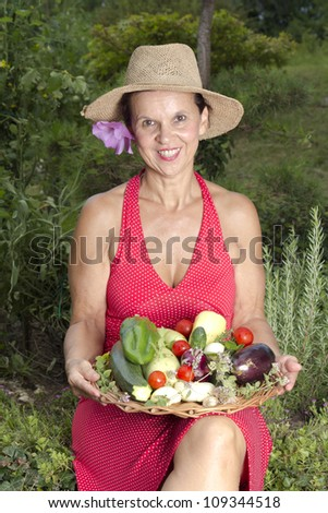 Mid age smiling woman with straw hat, showing  fresh vegetables  in her garden, on sunny summer afternoon
