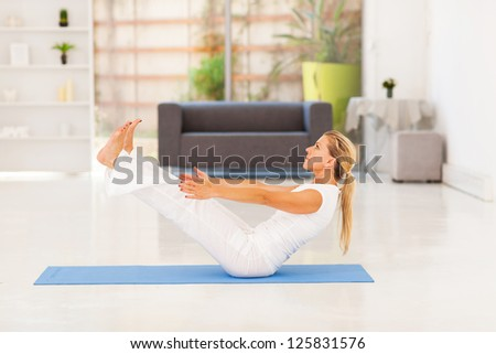 mid age woman doing yoga exercise at home - stock photo