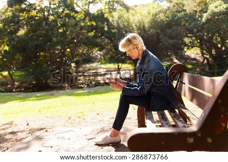 mid age woman using smart phone at the park sitting on a bench - stock photo