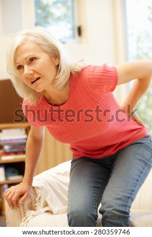 Mid age woman with backache - stock photo