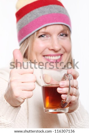 Mid age Woman With Hot tea Wearing Winter Clothes showing thumbs up on a white background - stock photo
