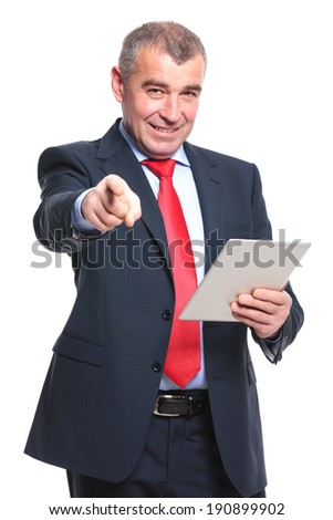mid aged business man holding a tablet in his hand while pointing and looking at the camera with a smile on his face. isolated on a white background - stock photo