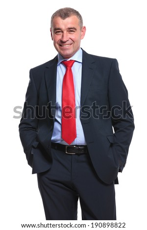 mid aged business man smiling for the camera while holding both hands in his pockets. isolated on a white background
