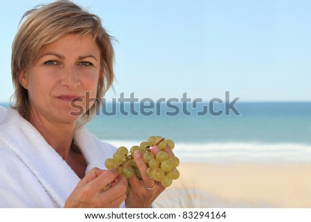 mid aged woman eating grapes near the sea - stock photo