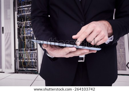 Mid section of a businessman touching digital tablet against data center - stock photo