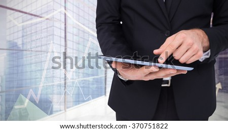 Mid section of a businessman touching digital tablet against stocks and shares