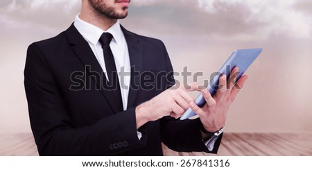 Mid section of a businessman using digital tablet pc against clouds in a room - stock photo