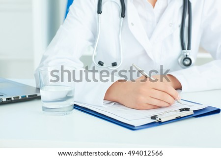 Mid section of a female medicine doctor hand holding silver pen writing something on clipboard closeup. Physician ready to examine patient.