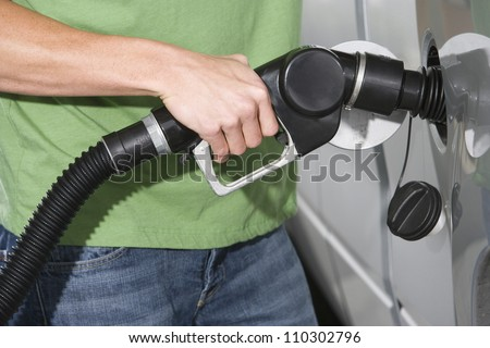 Mid section of a man refueling a car - stock photo