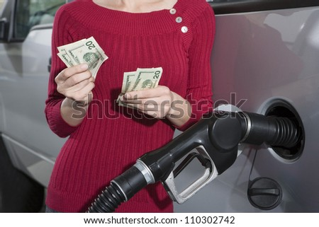 Mid section of a woman counting money while refueling car
