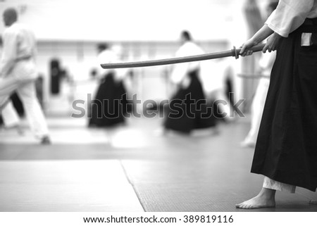 Mid section of a woman in hakama holding wooden bokken - stock photo