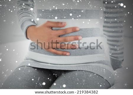 Mid section of a woman with stomach pain sitting in bed against snow - stock photo
