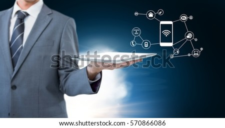 Mid section of businessman holding digital tablet with digitally generated connecting icons