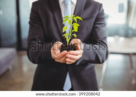 Mid section of businessman holding plant in office