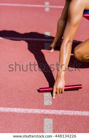 Mid-section of female athlete ready to start the relay race on the running track - stock photo