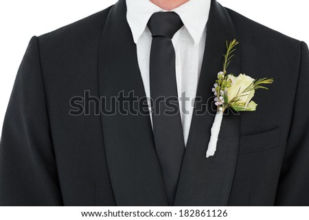 Mid section of groom wearing tuxedo with corsage over white background