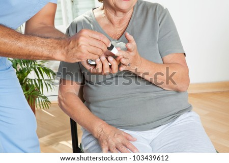 Mid section of male nurse checking sugar level of patient through glucometer - stock photo