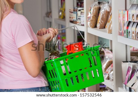 Mid section of mid adult woman carrying shopping basket in supermarket - stock photo