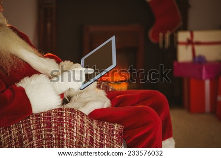 Mid section of santa touching tablet at home in the living room - stock photo