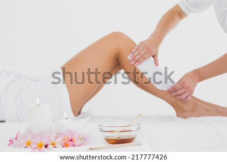 Mid section of therapist waxing womans leg at spa center - stock photo