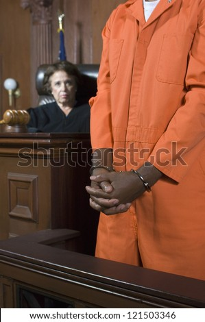 Mid section on a criminal standing in the witness stand with judge in the background - stock photo