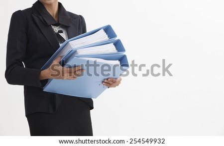 mid section on businesswoman carrying a stack of file - stock photo