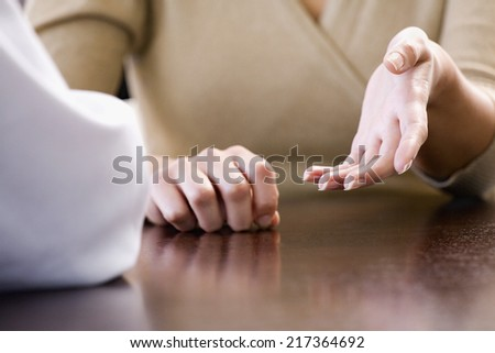 Mid section view of a businesswoman discussing with a businessman