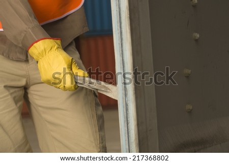Mid section view of a dock worker opening a cargo container