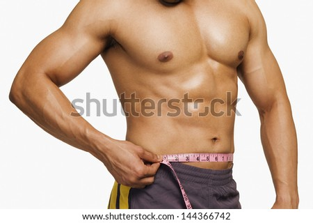 Mid section view of a man measuring his waist