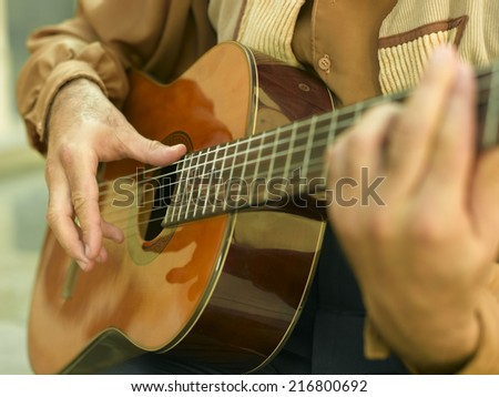 Mid section view of a man playing the guitar