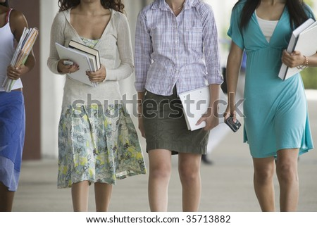 Mid section view of four teenage girls holding books and walking in the school campus