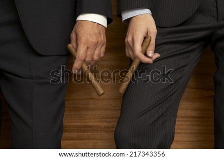 Mid section view of two businessmen holding cigars