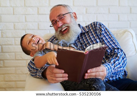 Mid shot of extremely positive grandfather and grandson while reading a funny book. Isolated over white background. Sitting in an armchair