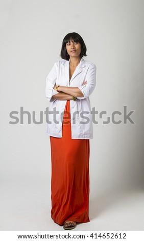 mid-twenty Filipino woman wearing a lab coat and a low cut orange dress - stock photo