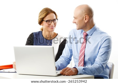 Middle age business woman and senior businessman sitting in front of computer and consulting while sitting at desk. Isolated on white background.  - stock photo