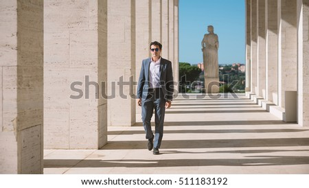 Middle age businessman full body portrait in Rome, Italy. Modern building as background.