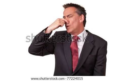 Middle Age Businessman in Suit Smelling Something Bad - stock photo