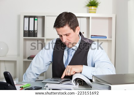 Middle Age Businessman Seriously Reading a folder at the sitting in his office - stock photo