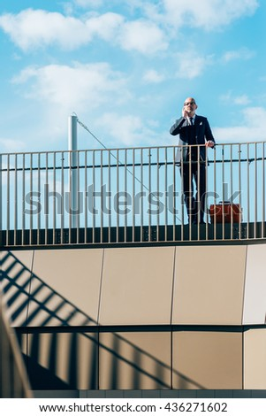 Middle-age contemporary businessman leaning on a handrail talking smart phone - work, business, conversation concept - stock photo