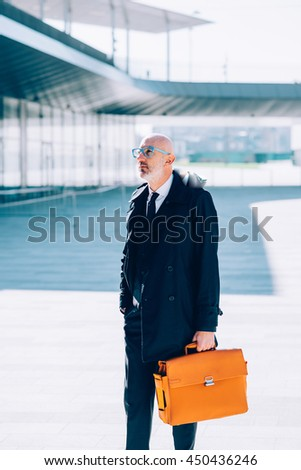Middle-age contemporary businessman walking outdoor in the city, holding a briefcase - business, career, manager concept - stock photo