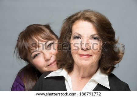 Middle age daughter andsenior  mother hugging and smiling with joy - stock photo