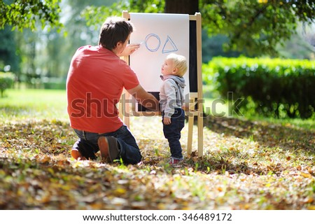Middle age father and his toddler son at blackboard practicing geometry