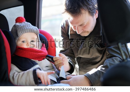 Middle age father helps his toddler son to fasten belt on car seat  - stock photo