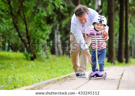 Middle age father showing his toddler son how to ride a scooter in a summer park