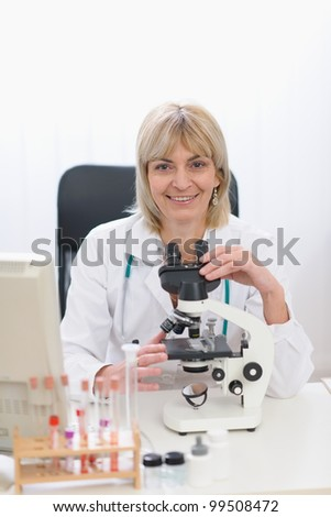 Middle age female researcher working with microscope
