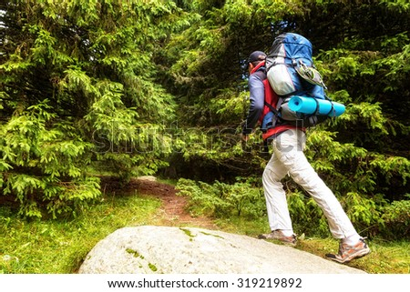 Middle age male backpacker deep inside forest. - stock photo